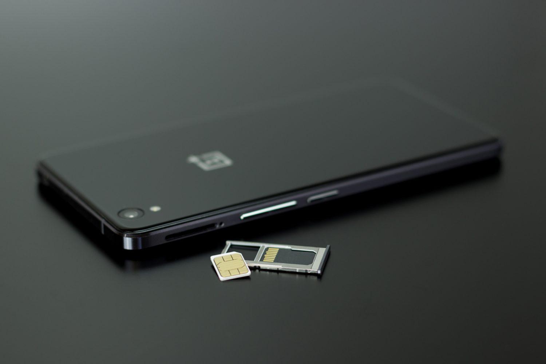 celular preto sobre uma mesa preta com o chip de celular ao seu lado representando o cartão de viagem da america chip