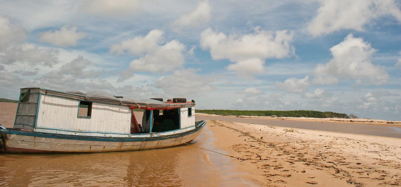 Paisagem de dunas e barco na água no Delta do Parnaíba, encontro do rio com o mar no nordeste brasileiro