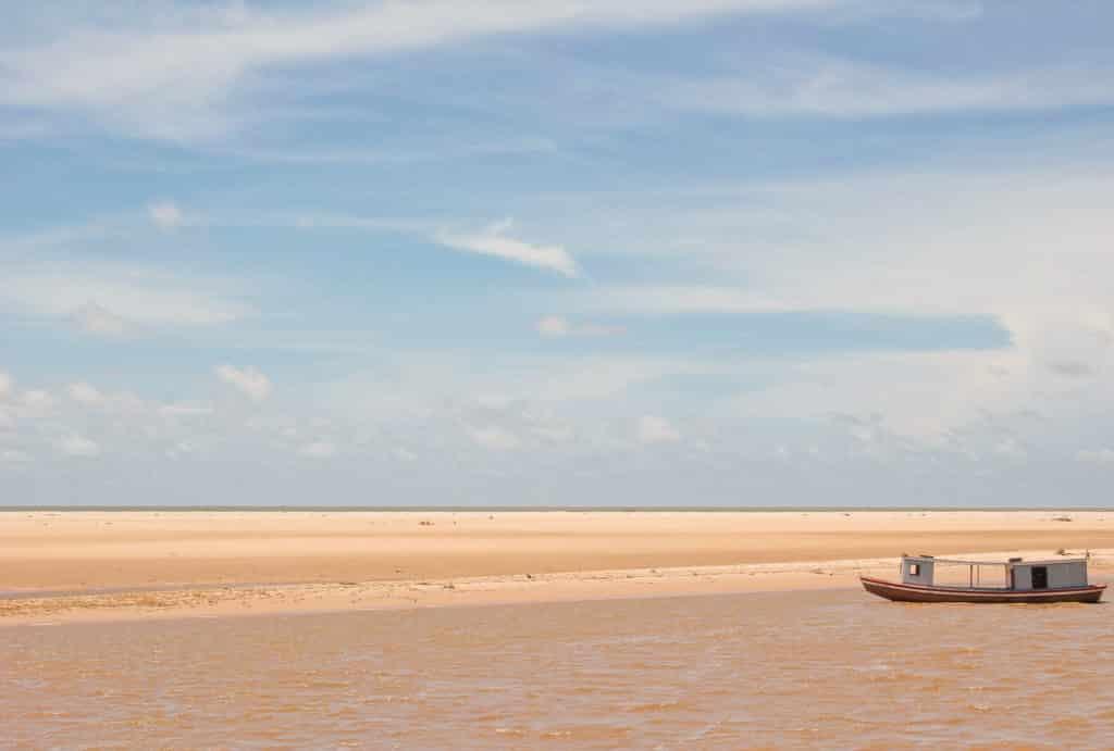 Foto de paisagem com areia e rio no Delta do Parnaíba, contrastando com céu azul