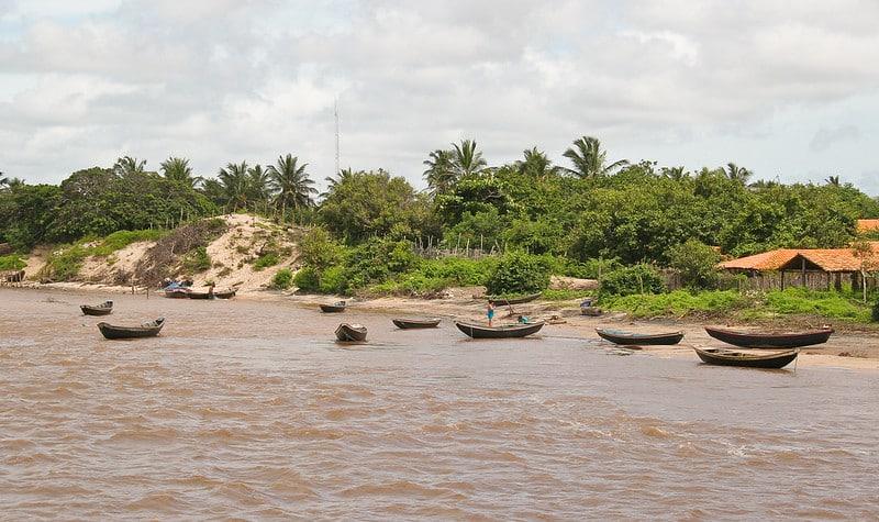 Foto de área rústica no Delta do Parnaíba, com barcos sobre as águas, pessoa parada na beira da água, rio turvo, e casinha em meio à mata