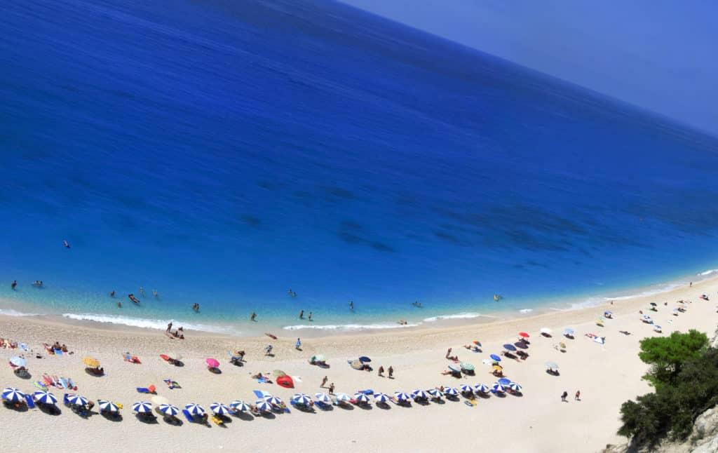 Foto de praia chamada Egremni, em Lefkada, com mar azul de cor profunda, mas águas límpidas, e alguns guarda-sóis na areia