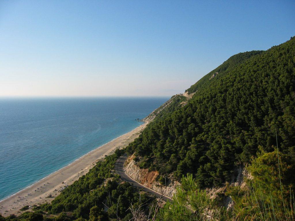 Foto de paisagem de Lefkada, com morro repleto de árvores, mar azul, faixa de areia branca e estrada cortando a montanha