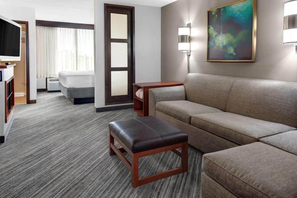Sala com sofá amplo, luminárias e quadro, em acomodação de dois ambientes no hotel Hyatt Place em Tampa, na Flórida, com parque da área com cama ao fundo.
