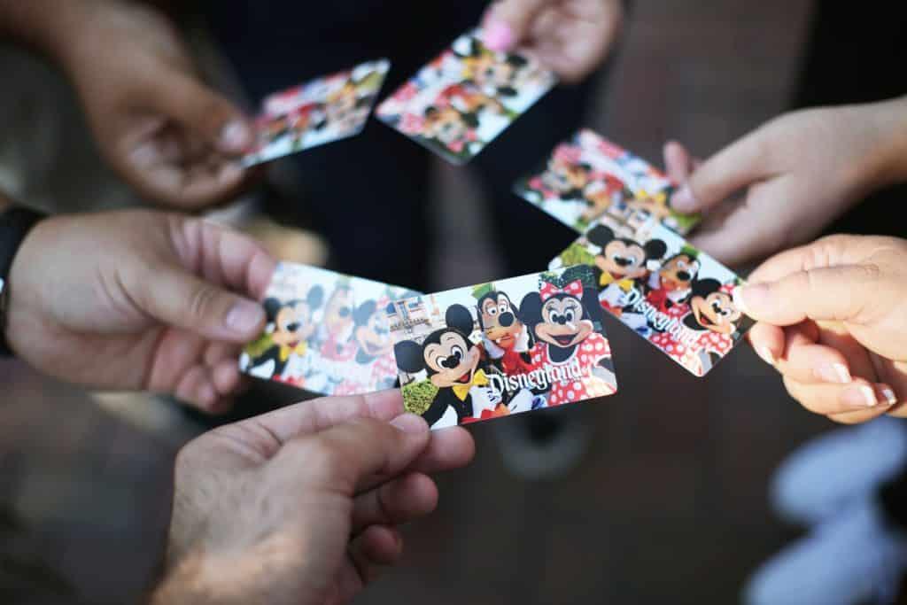 Mãos de pessoas segurando ingressos para a Disney