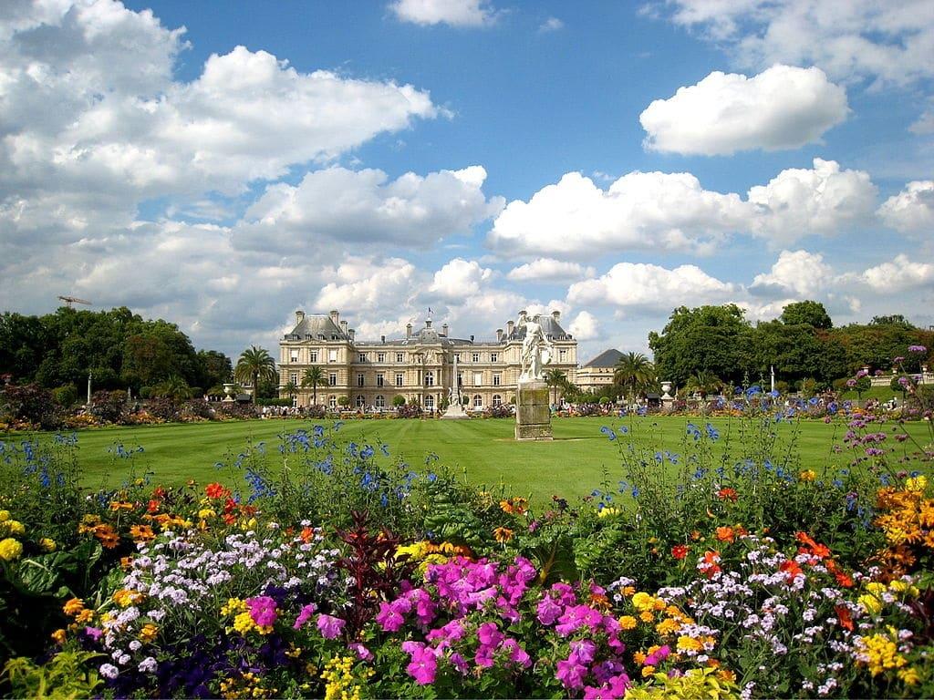 Foto do Jardim de Luxemburgo, um dos pontos turísticos de Paris, com flores coloridas em primeiro plano e palácio ao fundo