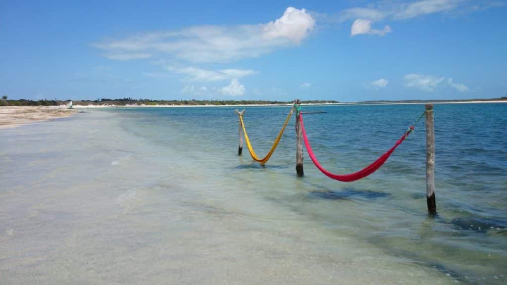 Praia em Jericoacoara, com duas redes de descanso em pilares no meio da água do mar, cena típica do destino