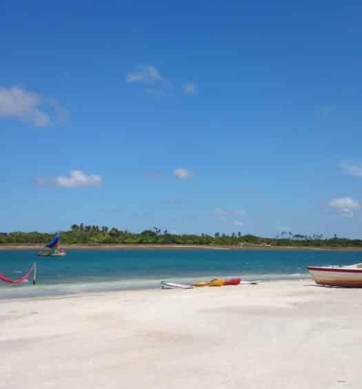 Jericoacoara, no Ceará, com praia de areia clara e mar azul turquesa, barco em dia de céu limpo e sol