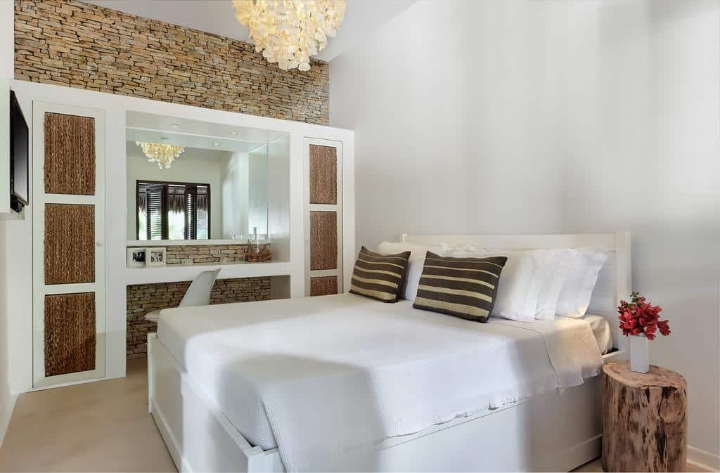 Quarto confortável da pousada La Villa Jeri, com cama ampla, TV e decoração rústica