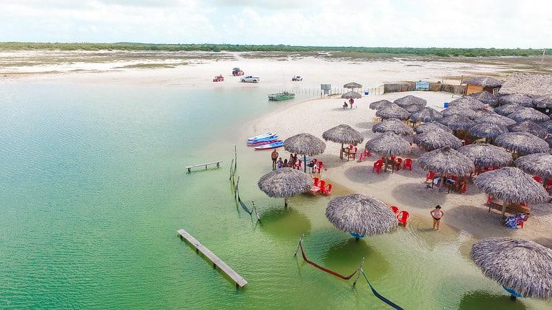 Foto de área com mesas, guarda-sóis e rede de descanso na Lagoa Azul, em Jeri, um dos destinos da Rota das Emoções