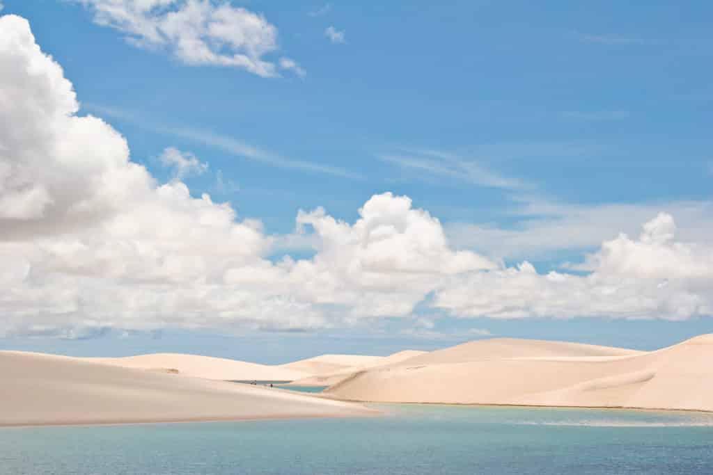 Os Lençóis Maranhenses em dia de céu azul com nuvens, com as dunas em volta de lagos de água clara
