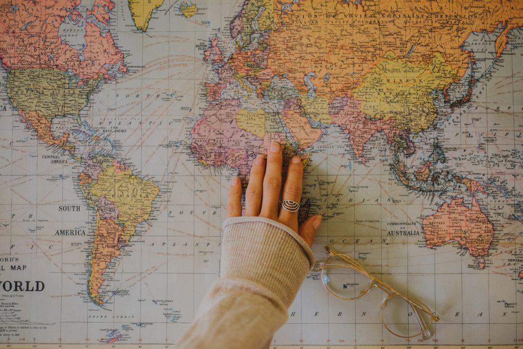 mão feminina procurando um país no mapa mundi colorido representando os países de cobertura da america chip