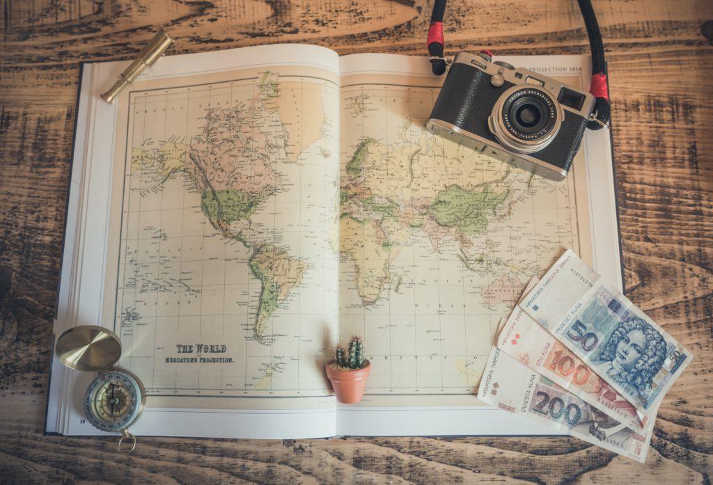 Foto de livro com mapa mundi, câmera fotográfica, notas de dinheiro e alguns outros objetos decorativos