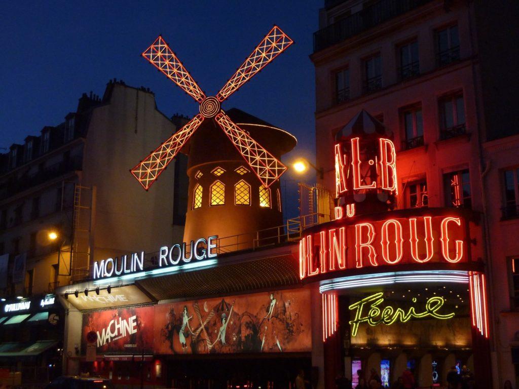 Moinho de vento e letreiros iluminados no Moulin Rouge, em Paris
