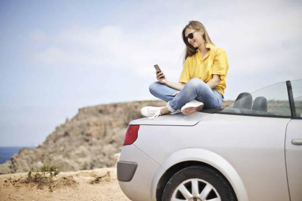 mulher sentada no capô do carro procurando qual cartão sim comprar
