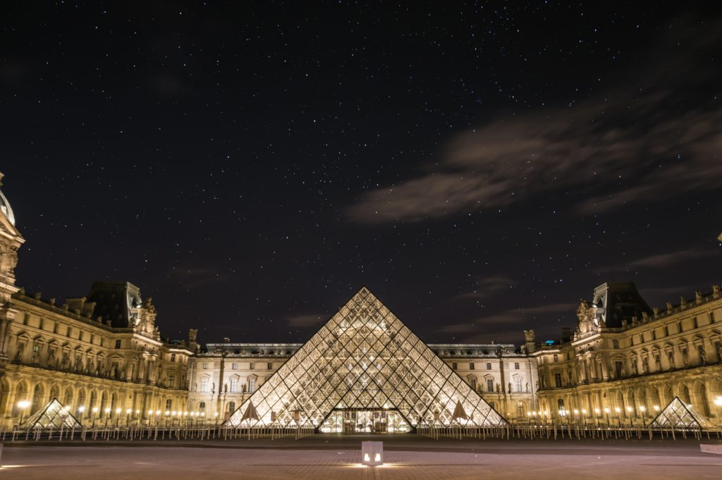 Museu do Louvre iluminado em noite estrelada, com pirâmide de vidro centralizada