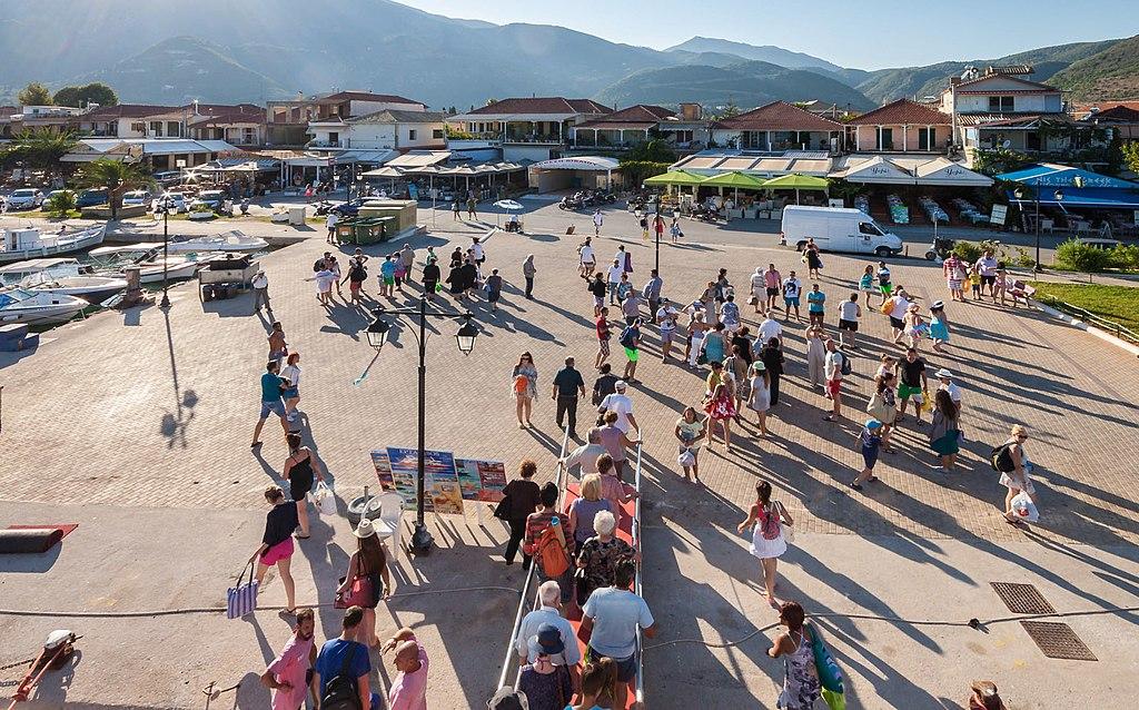 Pessoas circulando em pátio aberto da parte conhecida como Nidri, na ilha de Lefkada, Grécia