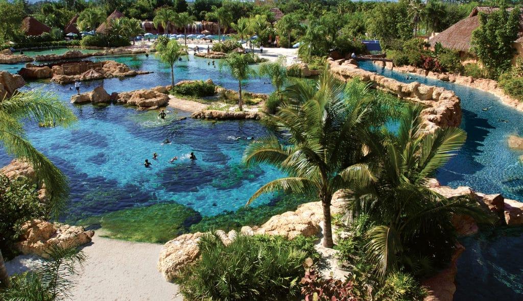 Foto panorâmica do parque Discovery Cove, com seus lagos e vegetação, além de pessoas nadando