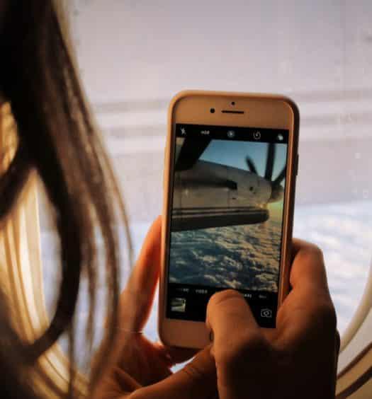mulher usando chip de celular para viagem internacional para fotografar a janela do avião