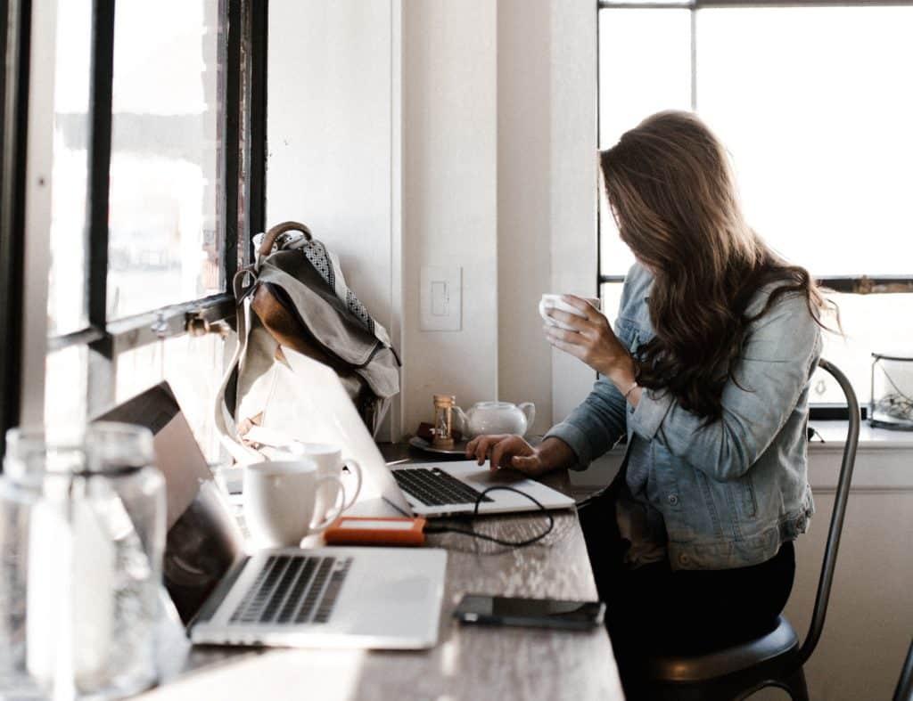 Mulher sentada em escritório, usando notebook e segurando uma xícara de café