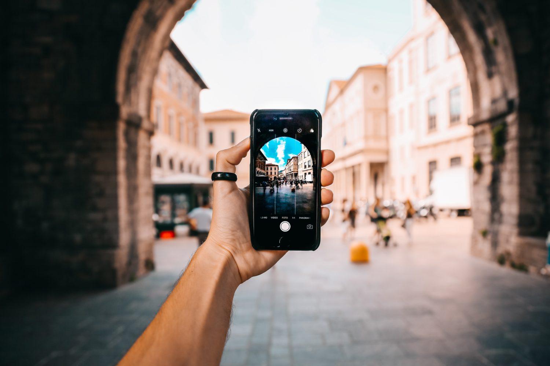 mulher segurando celular para tirar foto com seu chip de internet da europa