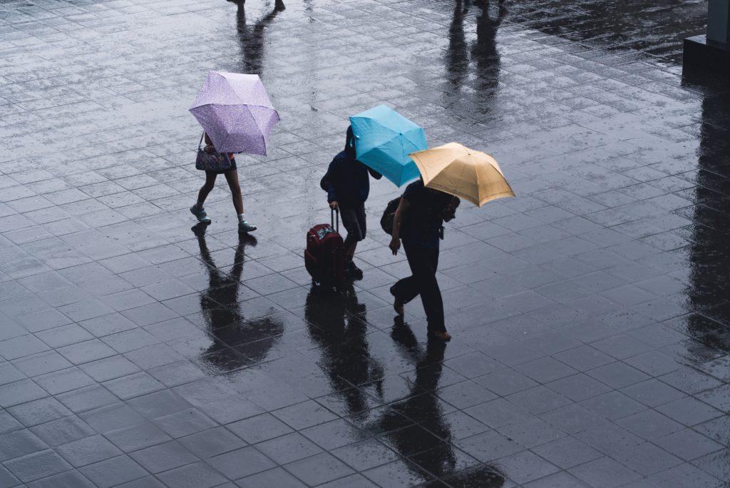 Três pessoas de guarda-chuva com mala, bolsa e mochilha, em dia chuvoso
