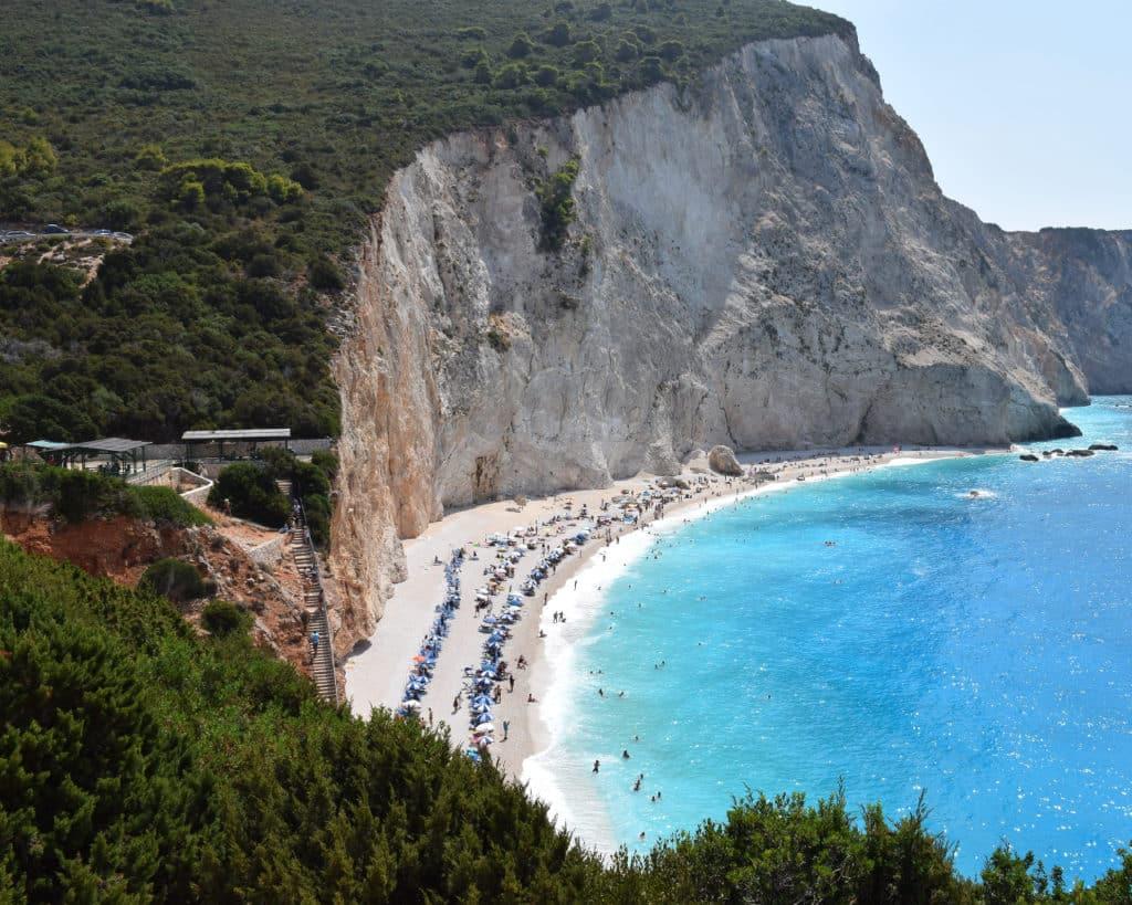 Foto ampla de Porto Katsiki, uma das praias mais famosas de Lefkada, com escadaria de madeira que leva à faixa de areia branca próxima ao mar cristalino de cor incrível