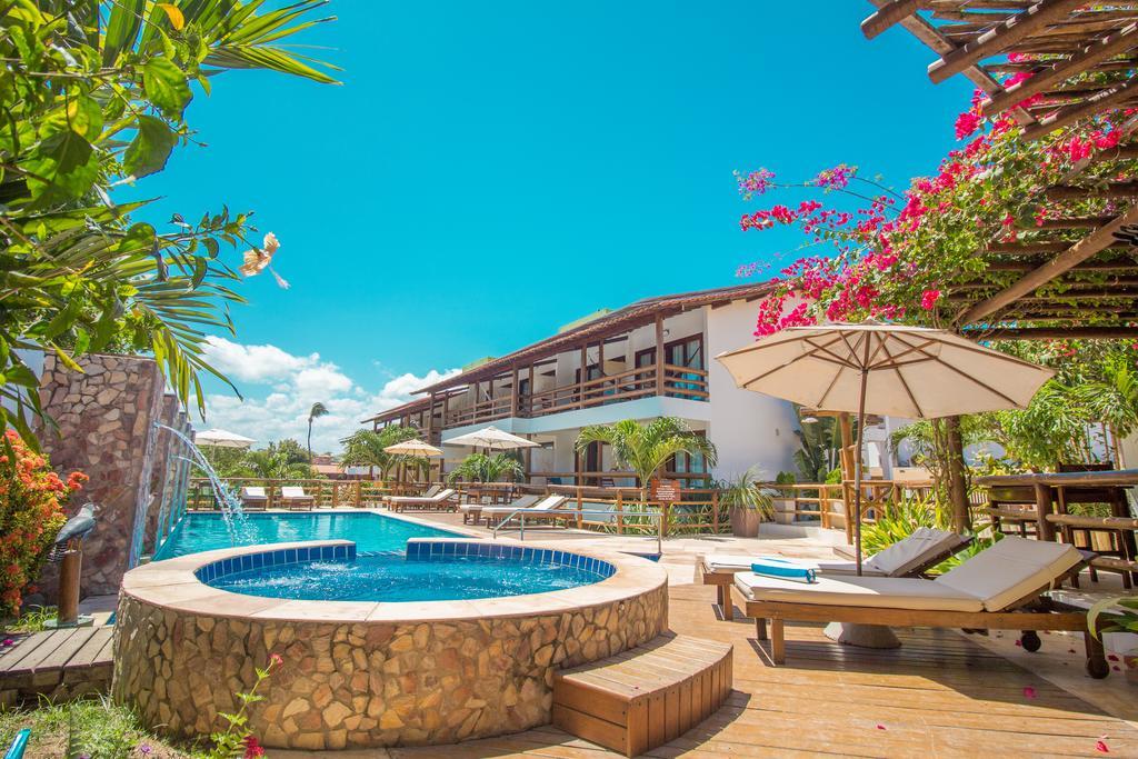 Foto de área comum da Pousada Carcará, com piscina, espreguiçadeiras, guarda-sol e o prédio com os quartos ao fundo