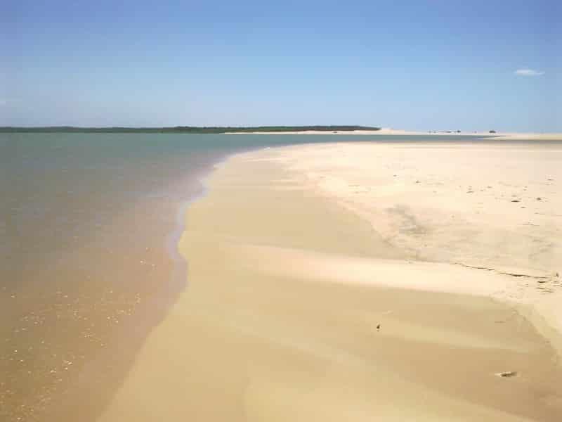 Foto panorâmica da praia de Barra Grande, no Delta do Parnaíba, com água límpida e areias claras, vazias