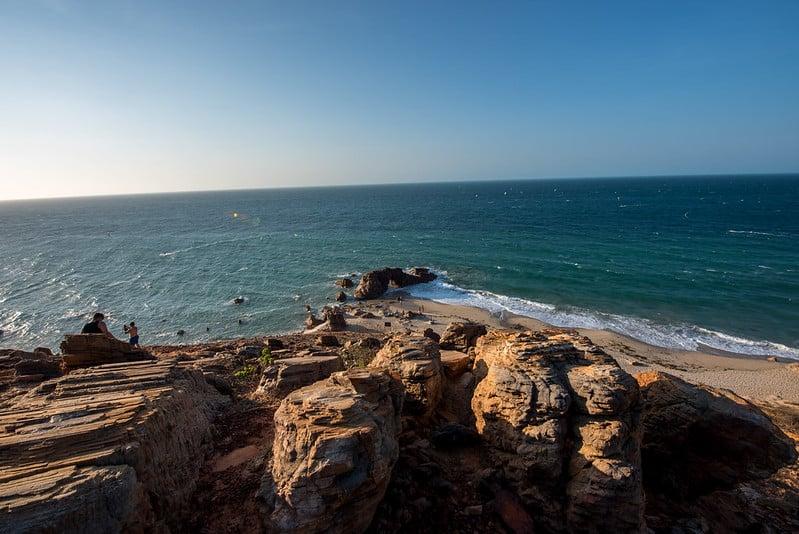 Praia em Jericoacoara em foto de cima, em um ângulo sobre pedras, com a Pedra Furada no meio e o mar ao fundo