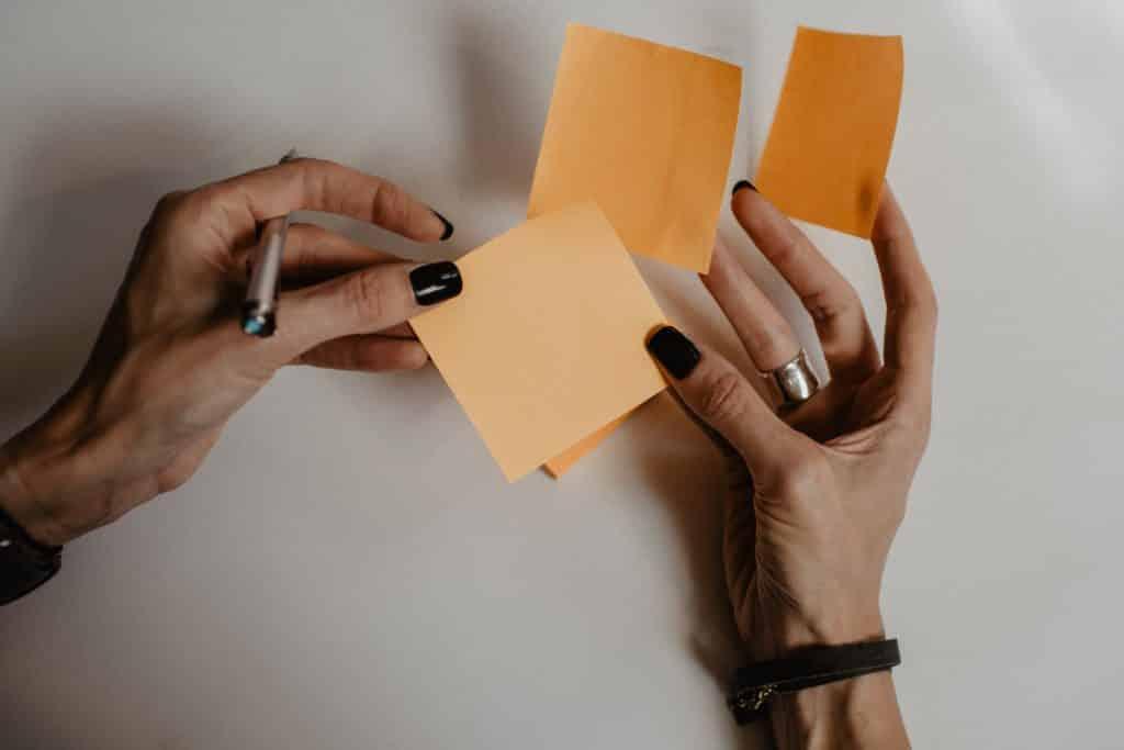 mulher segurando post it laranja - definindo qual seguro viagem escolher