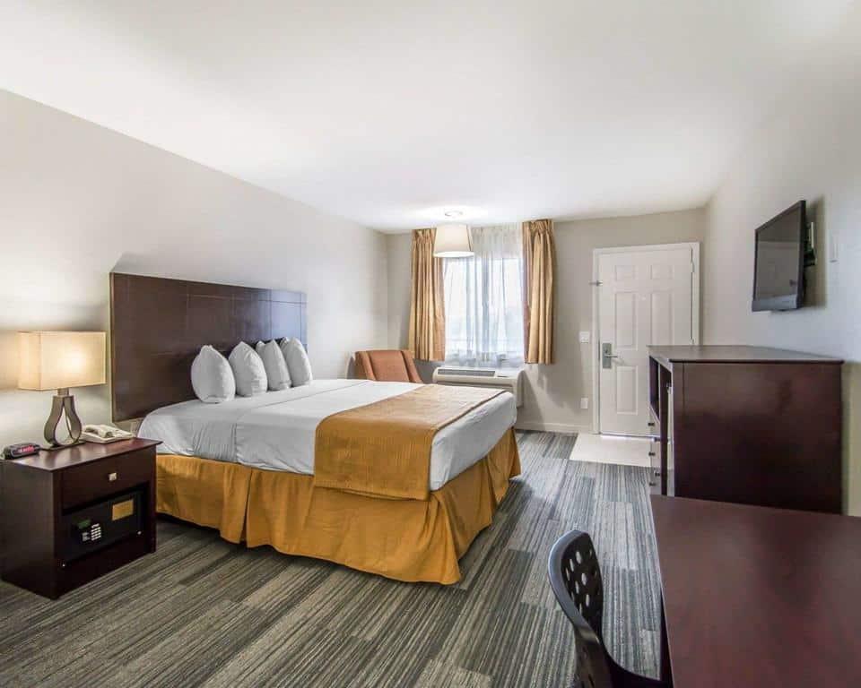 Foto de quarto com cama de casal, cortina e lençóis amarelos, e cômoda, escrivaninha e criado mudo, no hotel Quality Inn