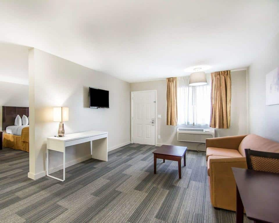 Segundo ambiente da acomodação no Quality Inn, com sofá, mesinha, abajur, e TV plana