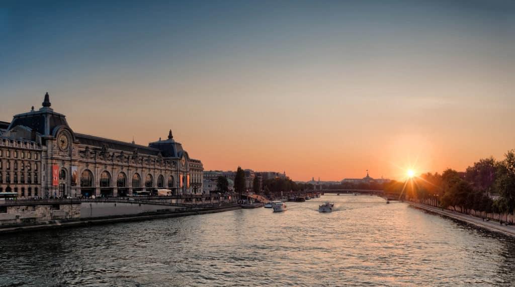 Foto de por do sol no rio Sena, com Museu de Orsay à esquerda, dois pontos turisticos em Paris