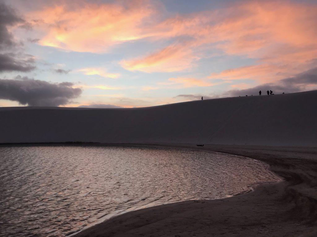 Foto de lagoa em destino visitado durante a Rota das Emoções, com dunas de areia e atmosfera de crepúsculo