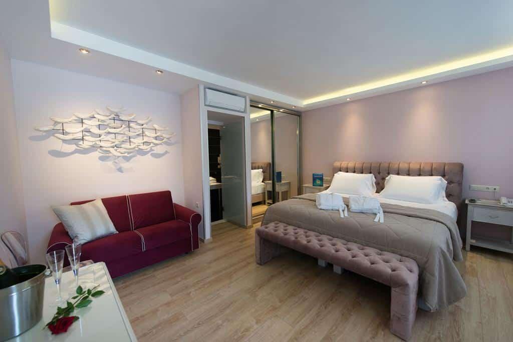 Foto de quarto espaçoso do resort San Nicolas com cama de casal ampla e sofá, atém de balde, rosa, taças e ar condicionado