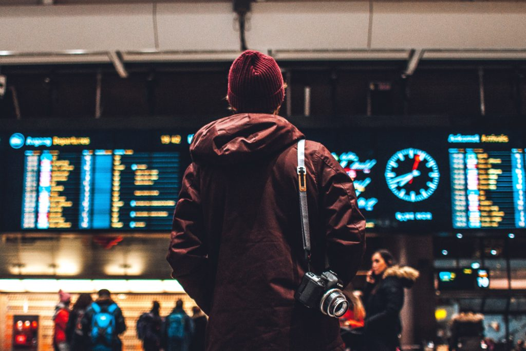 Pessoa, com câmera apoiada pela alça nos ombros, parada em frente ao painel com a lista de próximos voos em aeroporto