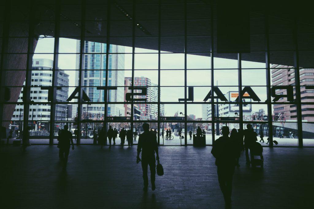Foto de aeroporto com pessoas circulando em pátio próximo das saídas, ilustrando post sobre seguro viagem anual