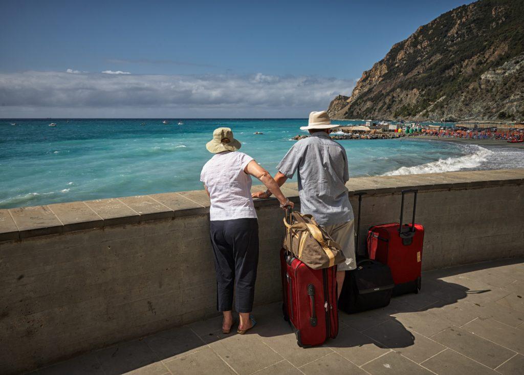 Foto de duas pessoas mais velhas segurando malas de viagem próximos a parapeito, observando o mar verde claro ao fundo - seguro viagem anual
