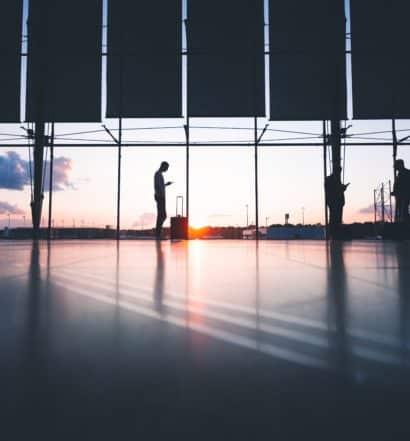 Pessoa com mala em frente à área de janelas de aeroporto, com o céu visto ao fundo, ilustrando a capa do post sobre seguro viagem anual