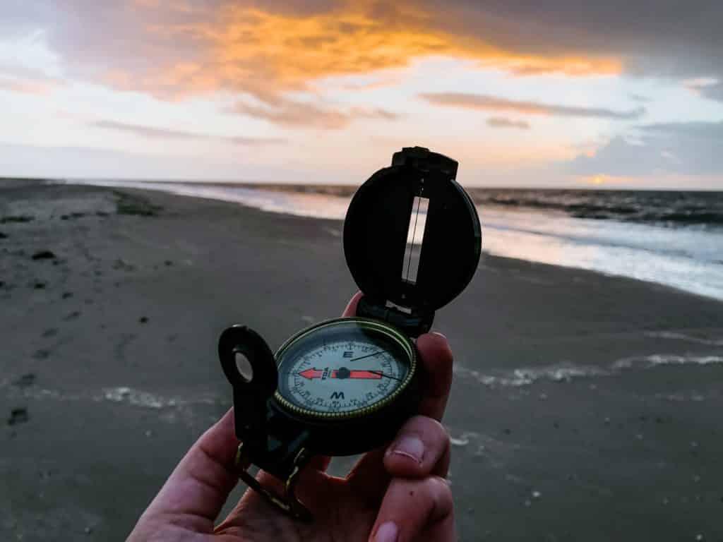 Foto de mão segurando bússola em frente ao mar - seguro viagem anual