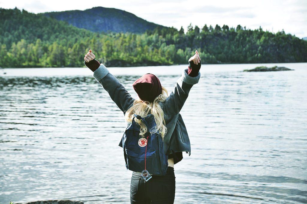 Mulher em frente a lago com os braços levantados, ilustrando post sobre seguro viagem para estudantes