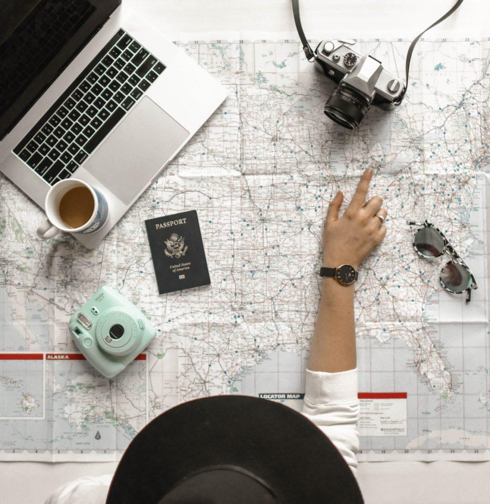 Pessoa com notebook, xícara de café, máquina fotográfica polaroid, máquina fotográfica analógica, óculos de sol e apontando para parte de mapa aberto sobre mesa