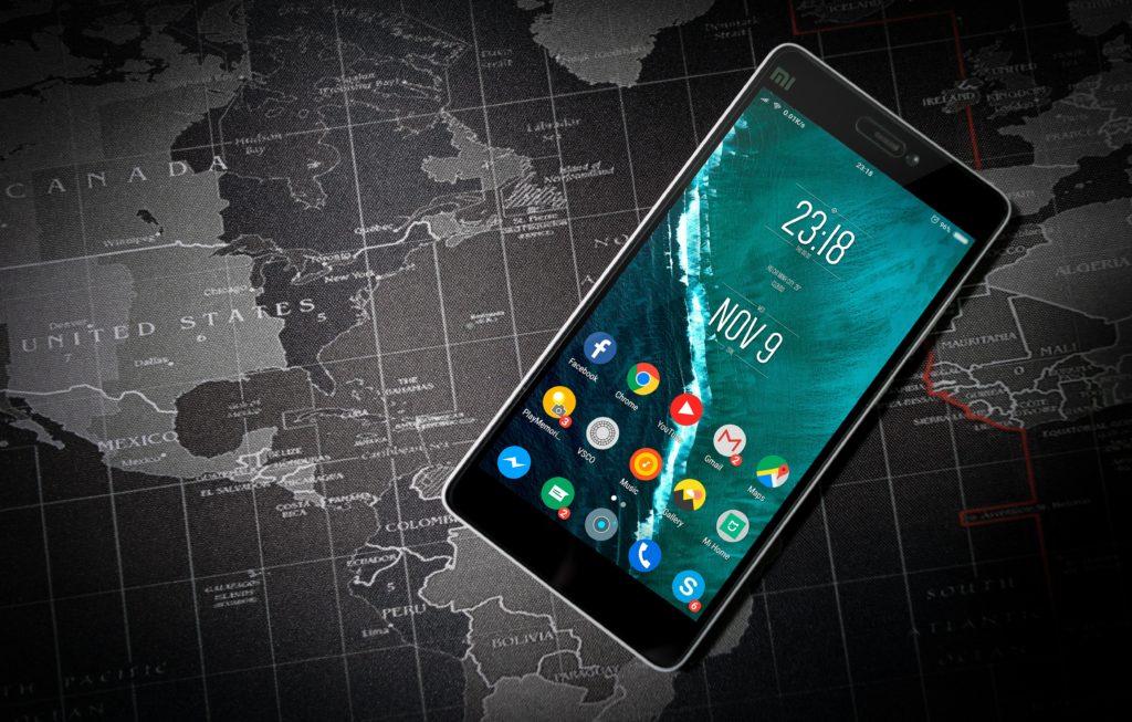 celular em cima de um mapa negro representando os países que a America Chip atende