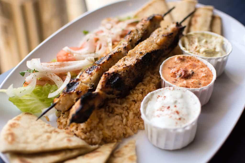 Prato típico da Grécia com dois espetos do famoso churrasquinho conhecido como souvlaki, três porções de molho coloridas, arroz, pães chatos e alguns legumes cortados