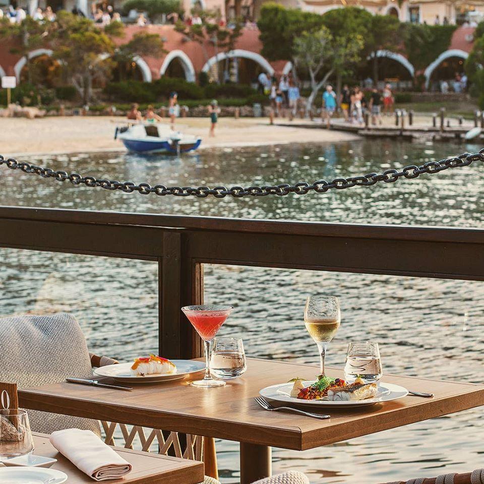 Mesa para dois, com taças de bebida, copos de água, e pratos, bem ao lado de parapeito de vidro com vista direta para água na Sardenha