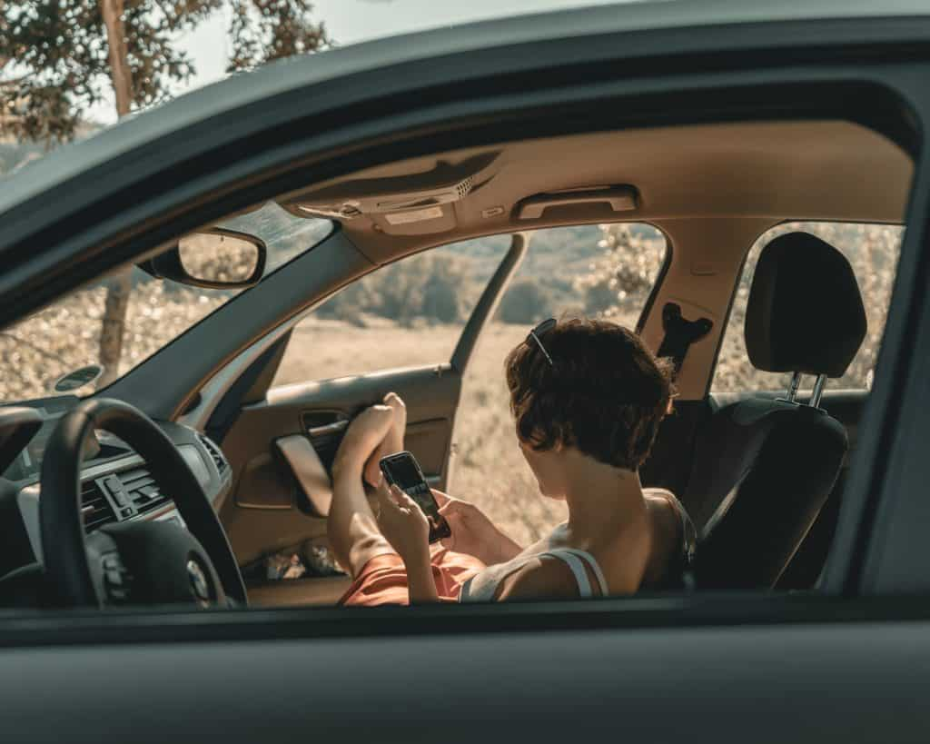 Foto de mulher sentada no banco do passageiro, com o carro parado, olhando no celular e com os pés apoiados na porta aberta