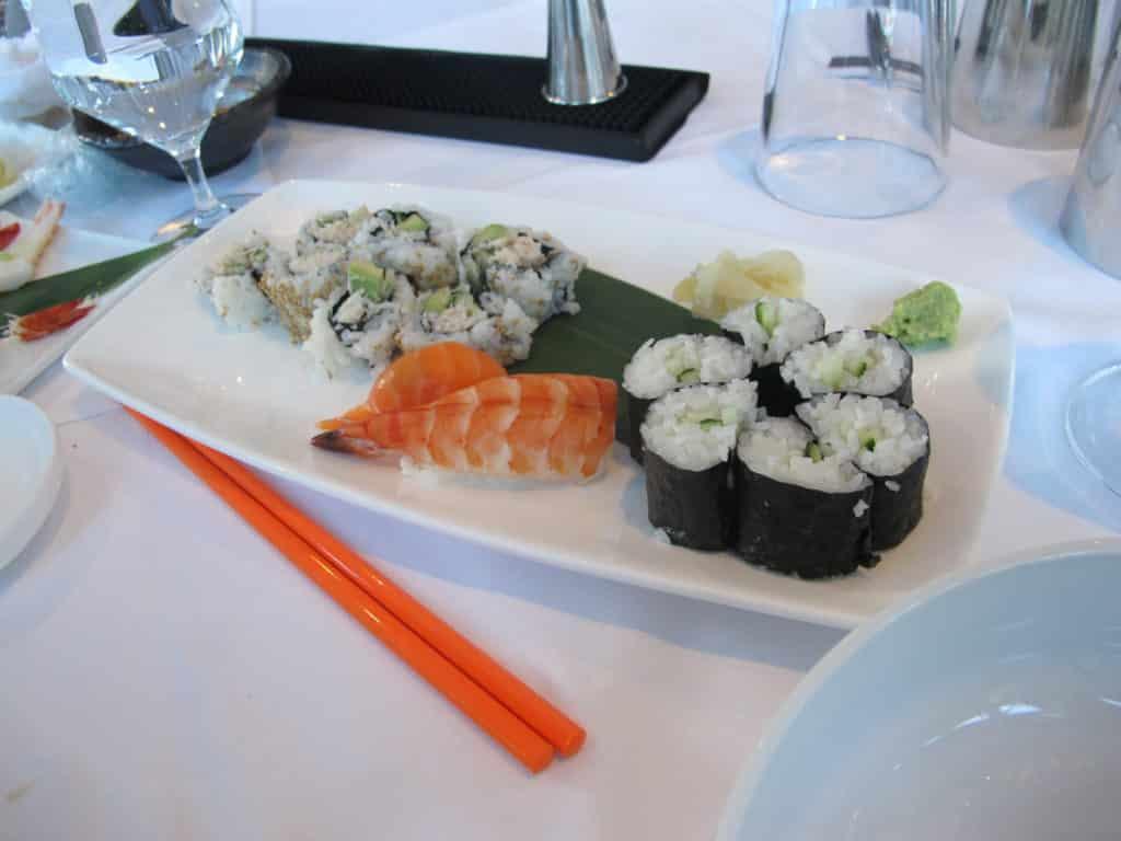 Foto de prato com algumas variedades de comida japonesa, e dois hashis à frente