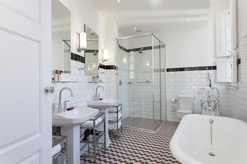 Banheiro de azulejos brancos, detalhes em preto, box de vidro e banheira, além de espelhos e pias duplas