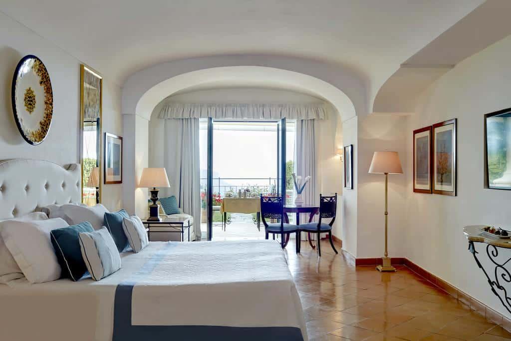 Quarto com decoração branca e detalhes em azuk, varanda com cortina e móveis finos no Belmond Hotel Caruso