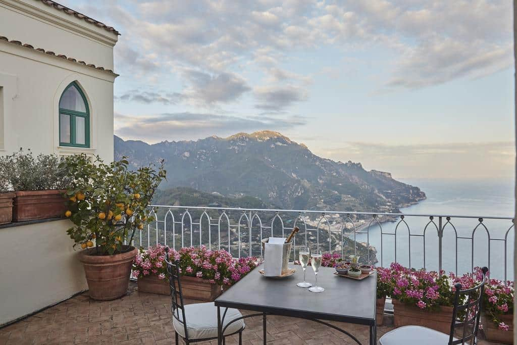 Varanda do Belmond Hotel Caruso, na Costa Amalfitana, com flores e limoeiro decorando o local e vista para o mar